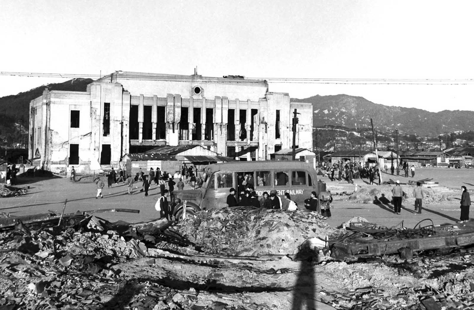 Civilians gather in front of the ruined Hiroshima Station, months after the bombing.