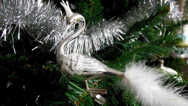 Zilveren zwaan in de kerstboom met een kroontje en mooie volle staart.