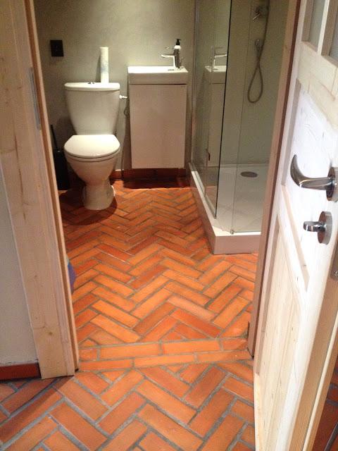 płytki z cegły na podłodze w łazience