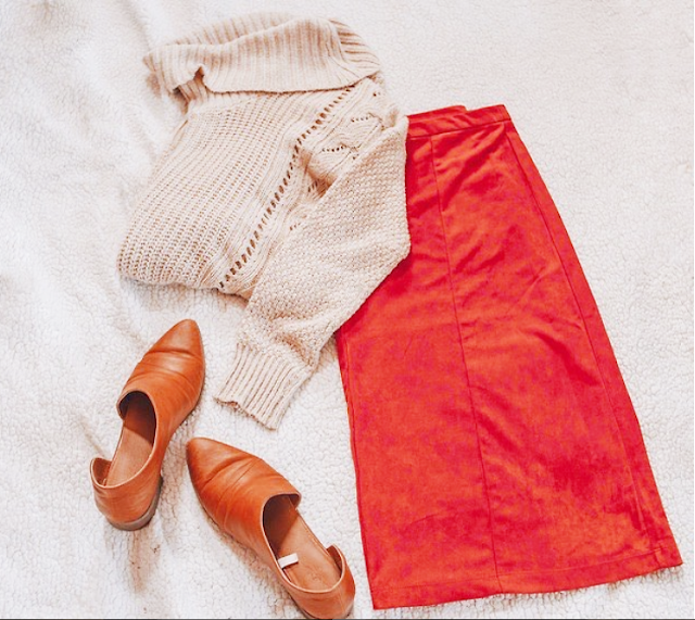 A flatlay of a cream cowl neck sweater, an orange suede midi skirt and brown d'orsay flats.