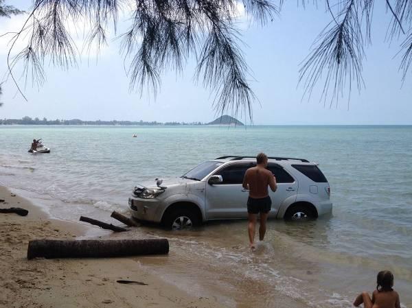 Мужчина идёт к джипу, который застрял на пляже