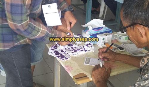 CELUP : Salah seorang pemilih dipandu petugas untuk mencelupkan jarinya ke dalam tinda ungu sebagai tanda sudah memberikan suaranya, Foto Asep Haryono