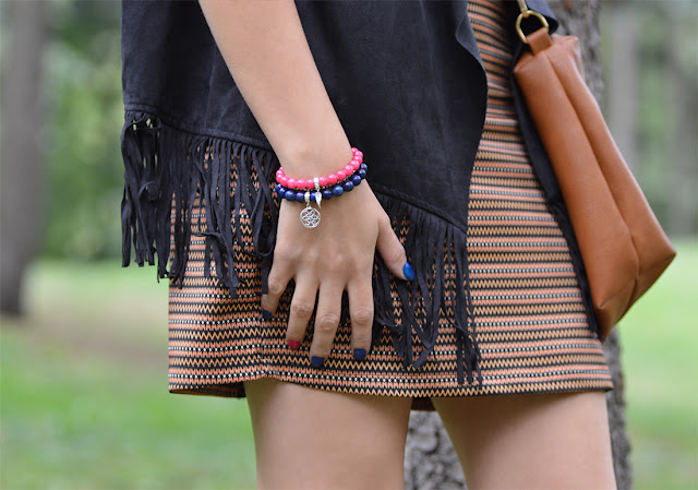 kolorowy zestaw trzech bransoletek z kamieni naturalnych, kamizelka z frędzlami i wzorzysta spódnica