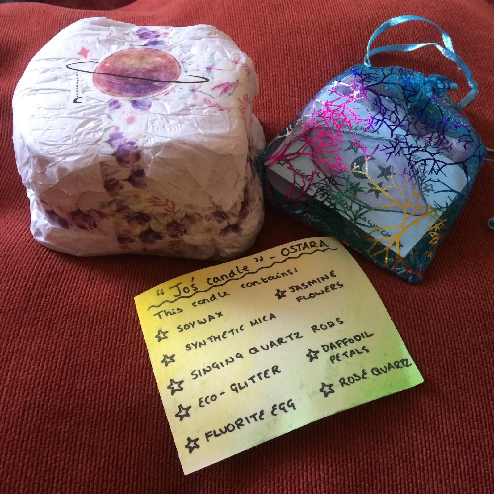 A photo of how my Ostara candle was wrapped, with tissue paper around it taped with washi tape, a pouch of tea lights and wrapped candles next to it, showing the Southern Sea Witch logo card inside, and in front of them both, a yellow and green watercoloured piece of card, handwritten with a list of what is contained in the candle