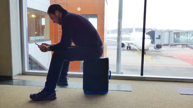 Taking a seat on the Jurni case at Tallinn Airport - MyJurni