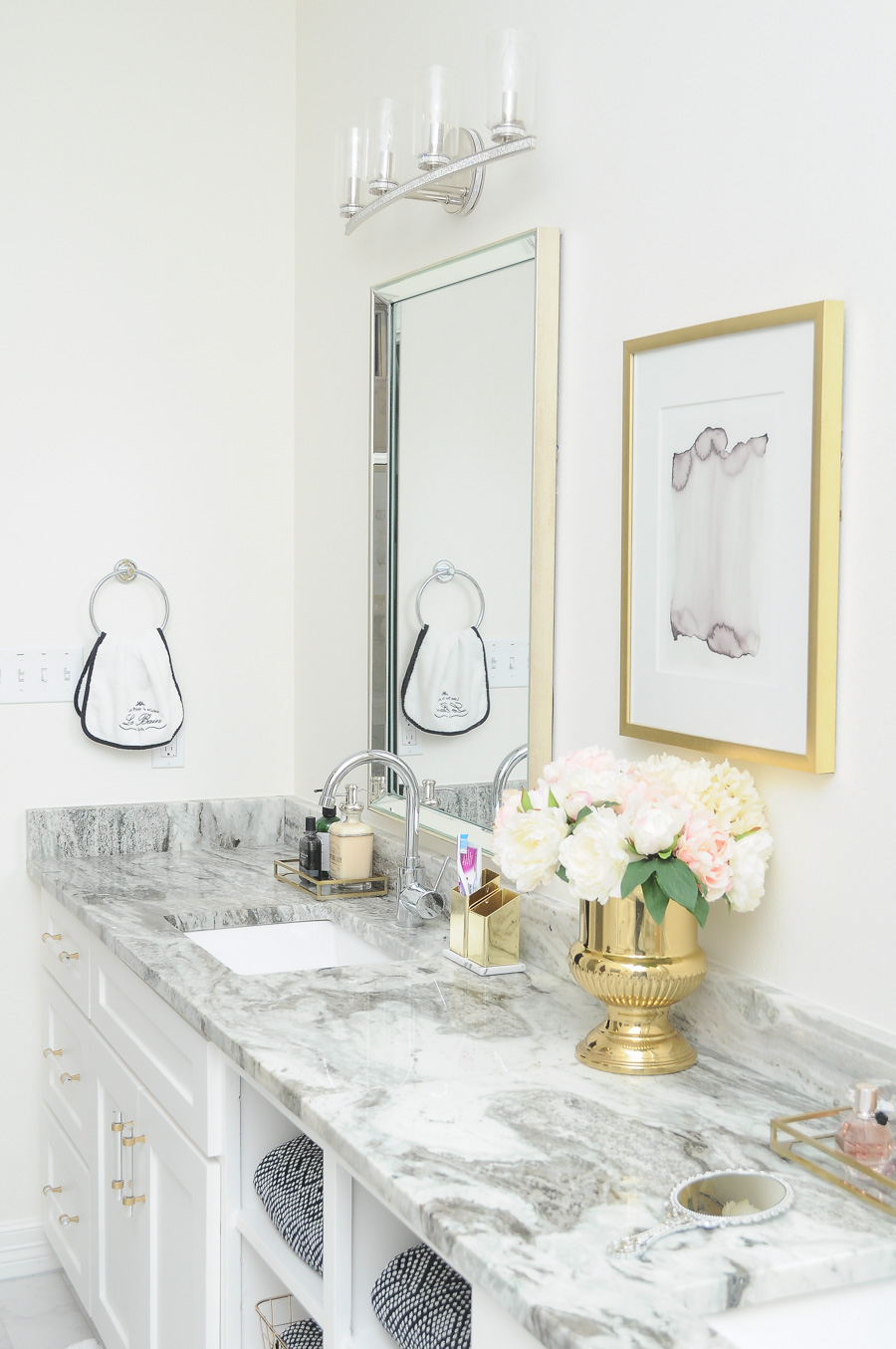 Black and white decor accents pair well with the bright white and gold color palette in this master bathroom. So many glamorous and sparkling touches!