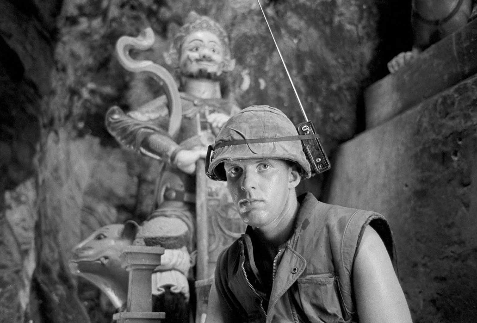 Marine Lance Corporal David L. Cruz tunes into the latest news on the Apollo moon shot on a helmet-mounted transistor radio while standing guard at Da Nang's Marble Mountain, on July 17, 1969. In background is a tall Buddhist figure found in many limestone caves of the mountain.