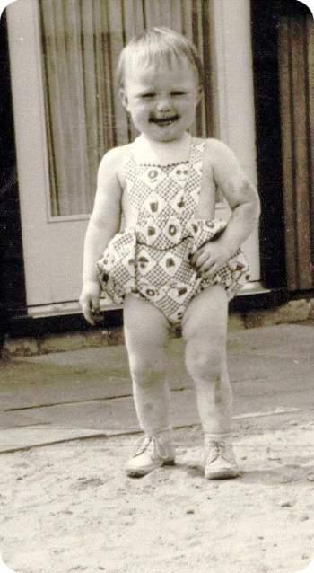 Ich im Alter von 2 Jahren im sandigen Hof, bein- und armfrei gekleidet, mit Schokolade um den Mund herum und an den Fingern sowie dreckigen Armen und Beinen.
