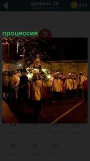 В вечернее время идет процессия священнослужителей с крестом