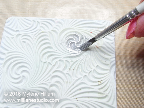 Brush the surface of the texture mould with the silver powder. Leave some areas lighter and some areas uncovered.