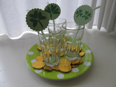completed paper straw tags for St. Patricks Day in glasses on a plate with gold coins