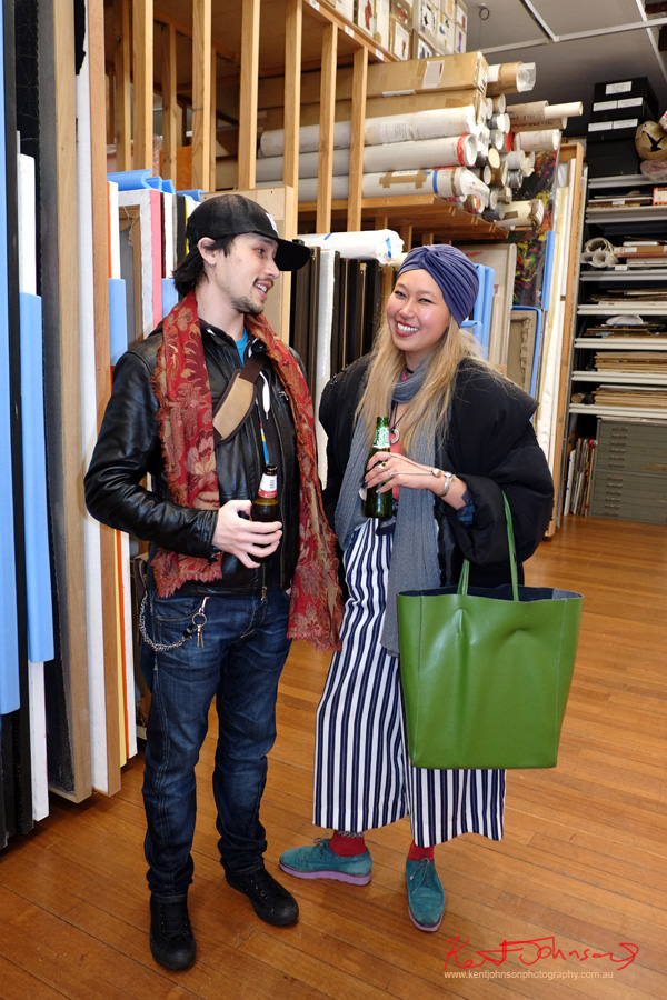 Him - Gym boots, jeans, black leather biker jacket, red floral scarf, baseball cap. Her - Large striped pants green leather tote, bulky jacket and turban. Street Fashion Sydney.