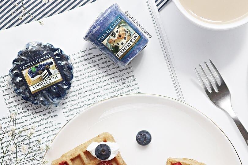 sampler (votive) yankee candle blueberry scoone na tle gazety obok białego talerza z goframi z jogurtem, jagodami i truskawkami