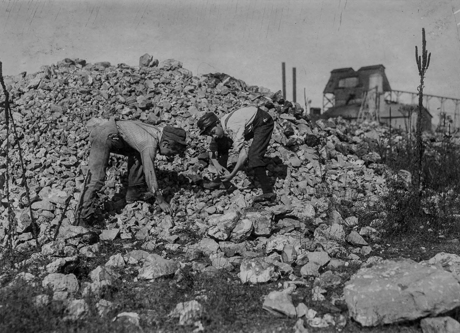 Basil Roberts and James Hopper, both 12, cull through waste from a zinc mine in Aurora, Missouri. 1910.