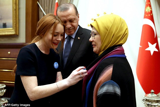 Lindsay Lohan places a badge on the jacket of Emine Erdogan