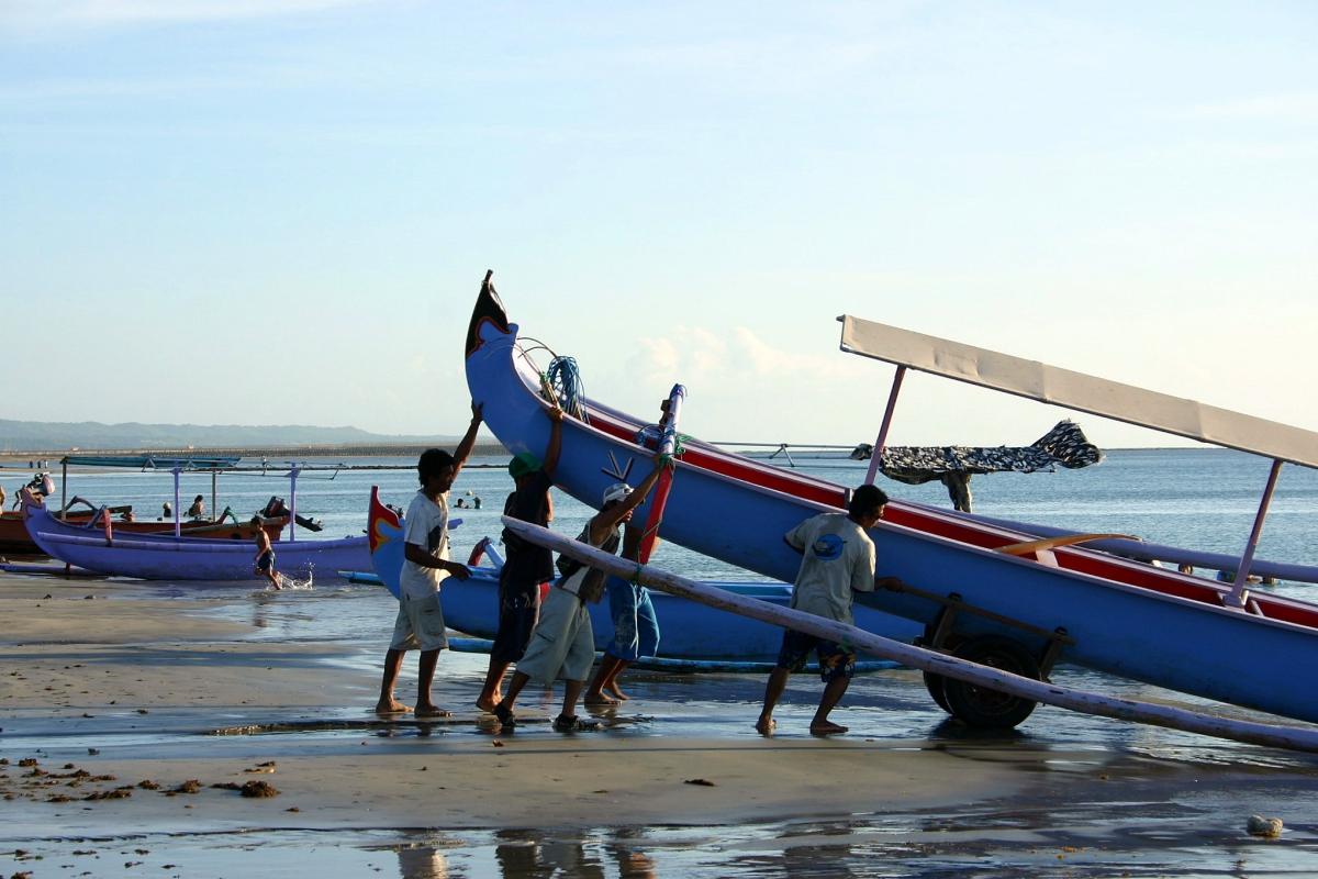 사람들에 의해 해변으로 올려지고 있는 보트