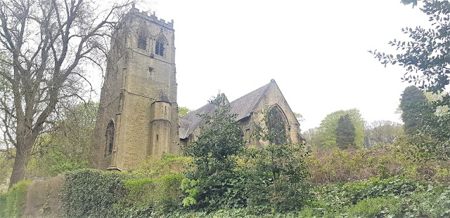 The tower of St John's Church, Holmfirth sticking up from behind green foliage.