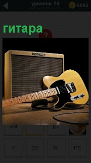 На столе стоит старинный динамик и положена электрическая гитара, которую оставил музыкант