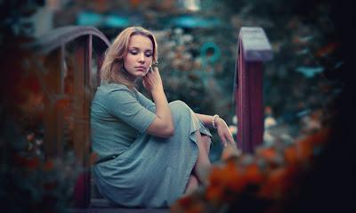 Linda rubia sentada en un pequeño puente de madera