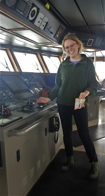 Photo of a smiling young woman standing on the bridge of a ship with her right hand resting on a large, horizontal control panel. Her hand is by a steering wheel about 6 inches in diameter. In the background are windows looking out onto the ocean.