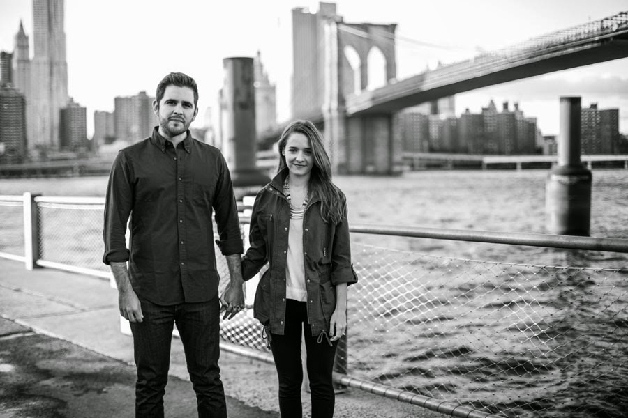 Black and white lifestyle engagement portrait of couple holding hands in Brooklyn Bridge Park- www.cassiecastellaw.com
