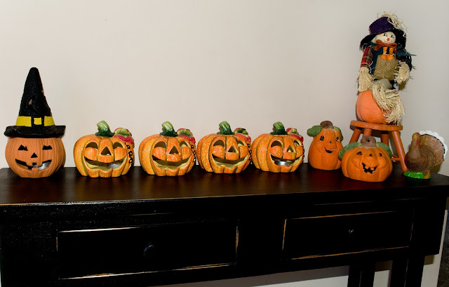 A row of ceramic jack-o-lanterns with a partnering turkey and scarecrow form a simple Halloween decor. These ones hold votive candles to make an eery display when it's dark.