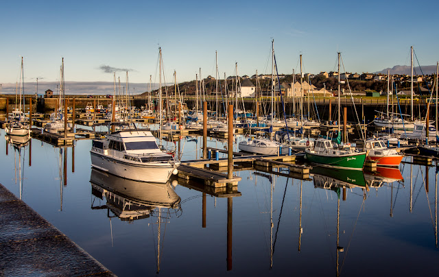 Photo of reflections in the still water at Maryport Marina