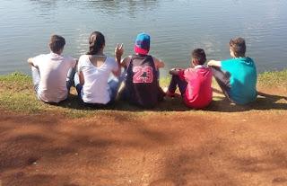 Grupo de amigos sentados à beira de lago.