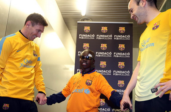 Mamadou Lamine with Lionel Messi and Andrés Iniesta during his visit to the Ciutat Esportiva