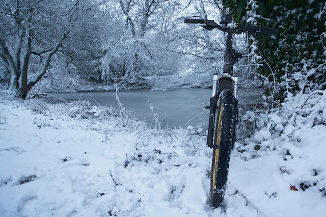 bike next to an ice covered pond in the snow