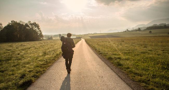 Парень идет с рюкзаком по дороге к солнцу