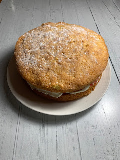 Large Victoria Sponge cake on a white plate on a white wooden table top