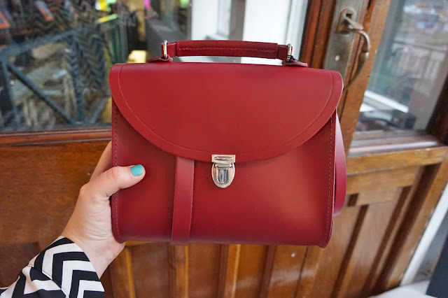hand holding red leather bag