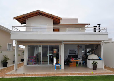 A elevação posterior da residência salienta a área de lazer integrada com a sala de jantar, sob um dos dormitórios do pavimento superior.