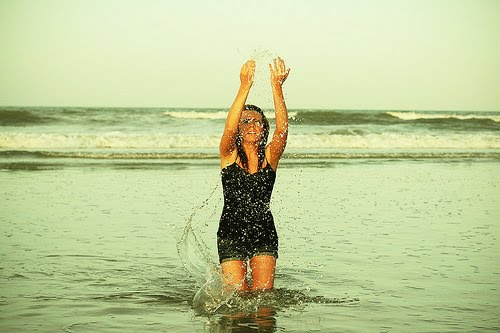 Mulher de pouca idade na praia beincando com a água do mar