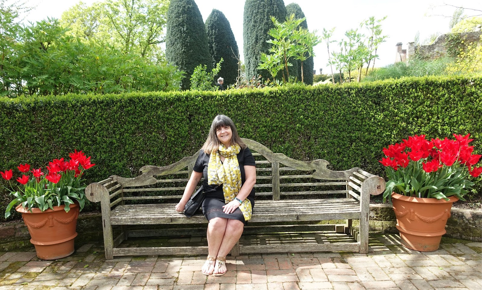 Woman on bench flanked by containers of red tulips at Sissinghurst Castle garden