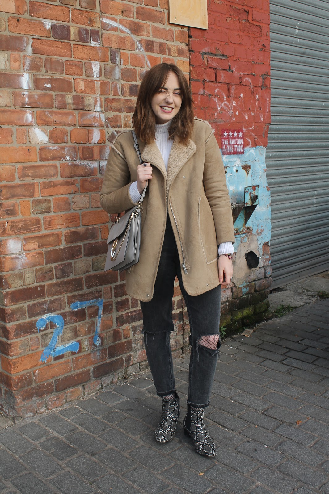 tan faux sheepskin coat from Pull & Bear, white rib roll neck jumper from ASOS, Chloe faye bag in grey copy, ASOS furlough jeans in washed black with busted knees over fishnet tights,  ASOS amber snake boots