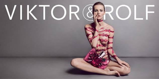 הדוגמנית יושבת על רצפה אפורה כשעל גופה ציור גוף של סרטים עם פפיונים בדוגמת הבושם בונבון.