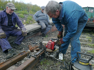 Ken drilling a rail, Les and Malcolm wait to plate the joint