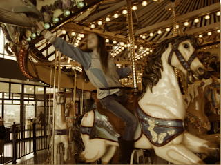 Child reaches for a brass ring on a carousel