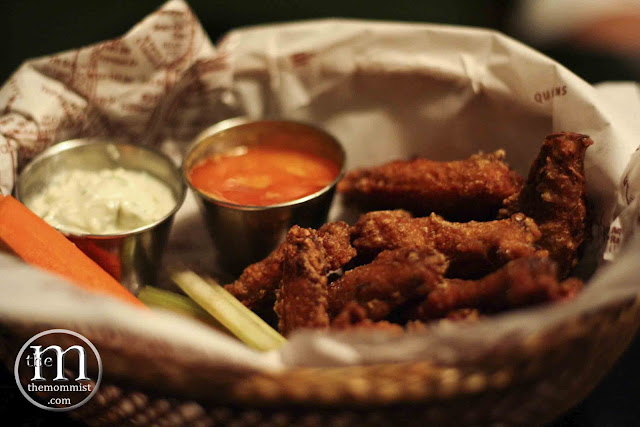 Buffalo wings in a basket with blue cheese dip and vegetable sticks