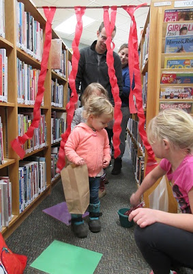 2 toddlers and their parents walk through the library stacks decorated to look like Candyland, while an older child hands out candy