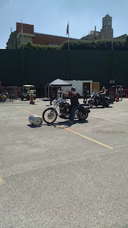 Woman riding motorcycle, rolling keg along parking lot with front wheel