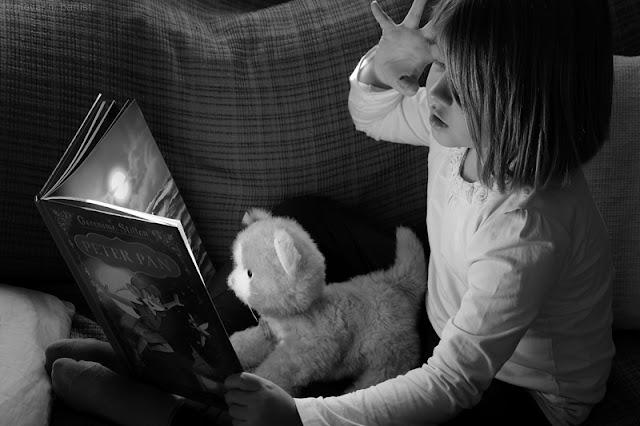 Bambina che legge una storia al gattino