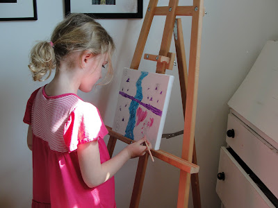 kid painting on easel