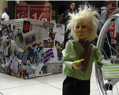 Still from the Life Outside the Box film, with puppet in front of disability box and beside a wheelchair