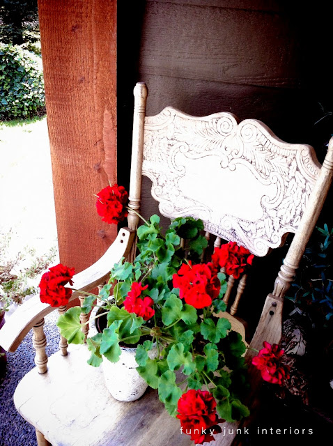 red geraniums on an old chair