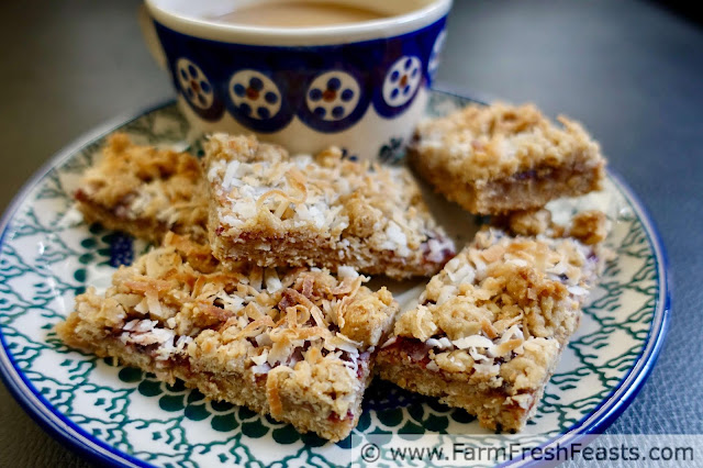 photo of a plate of Raspberry Oatmeal Coconut bar cookies with a mug of coffee