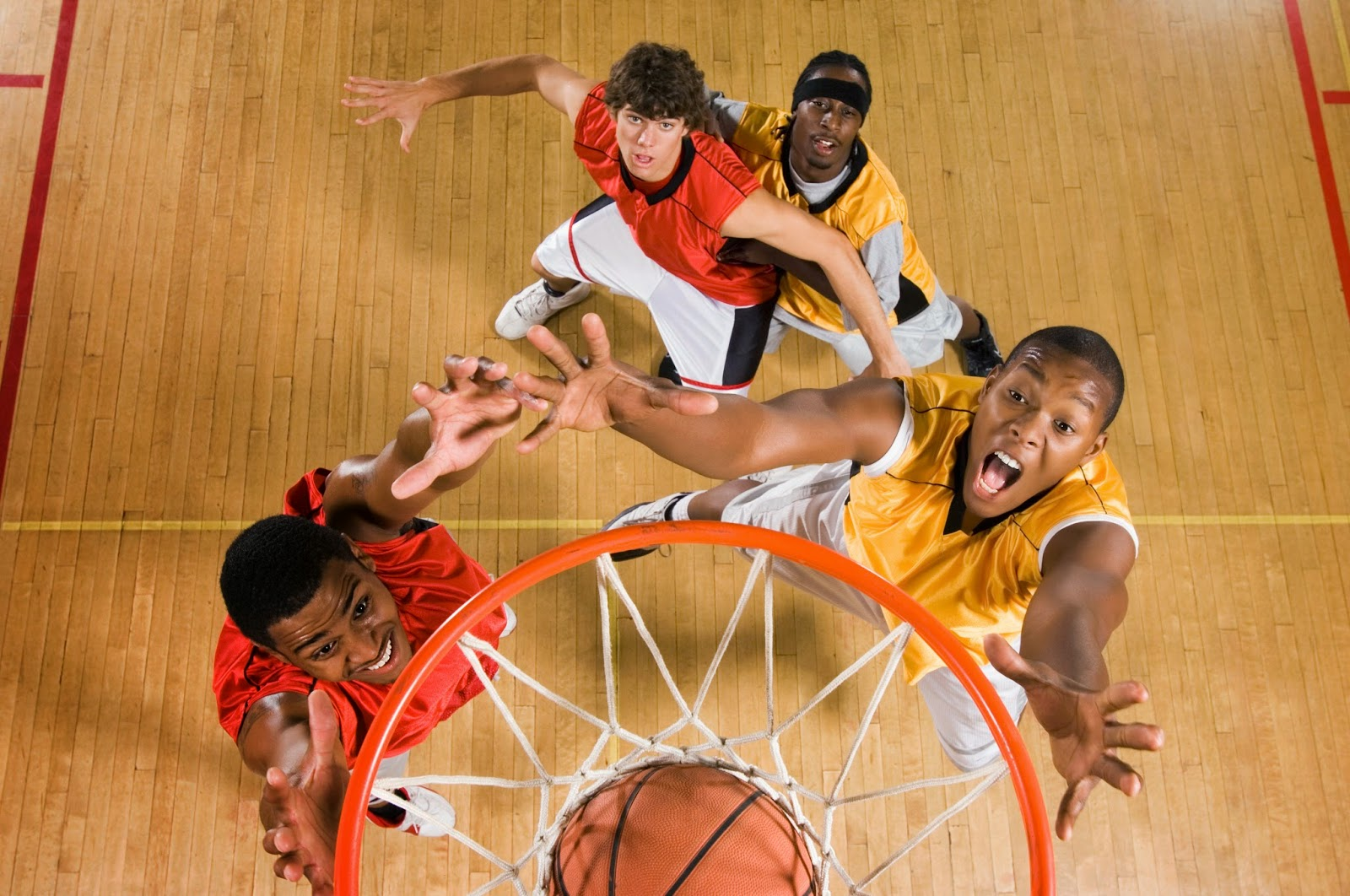 basketball players clamoring over ball near net