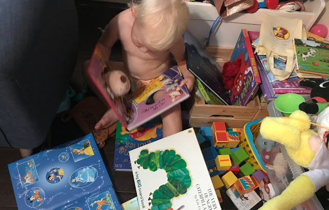 My toddler sitting on the floor reading a book surrounded by lots of books and toys